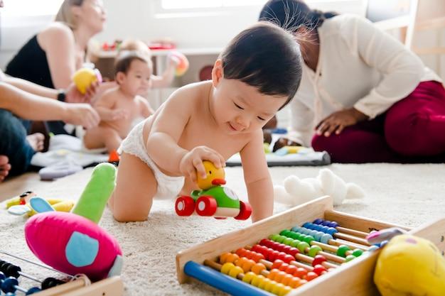 Bebé jugando con un carro de madera.