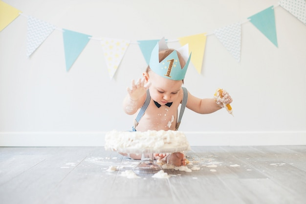 Bebé jugando con un pastel durante su fiesta de cumpleaños de pastel aplastante