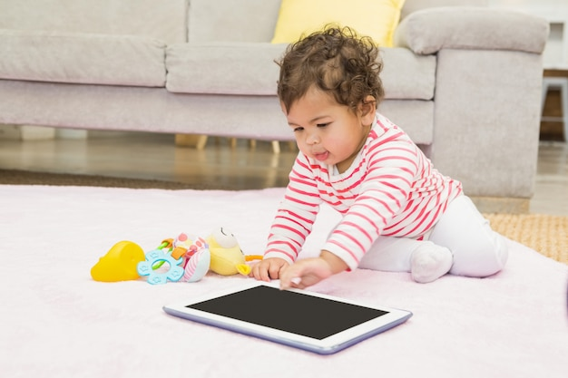 Bebé lindo en la alfombra con tableta en casa