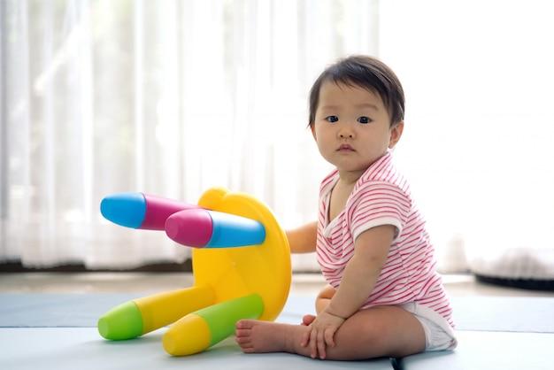 Bebé lindo asiático que sienta y que juega una pequeña silla plástica colorida en la estera suave en casa.