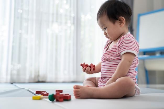 Bebé lindo asiático que sienta y que juega un pequeño juguete en la estera suave en casa.