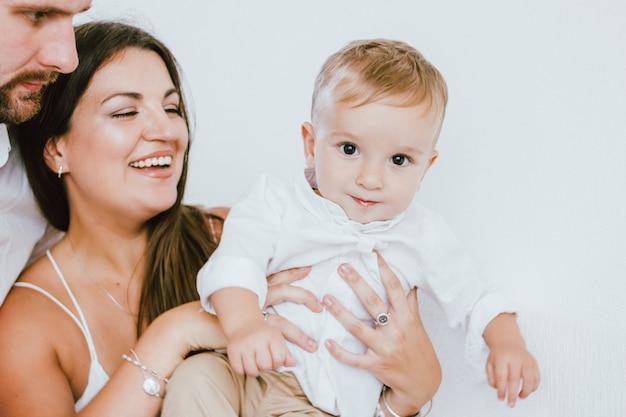 Bebé lindo en camisa blanca con su familia feliz sobre fondo blanco, retrato de cerca