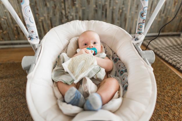 Bebé lindo con el chupete que miente en el carro de bebé en casa