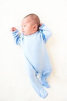 Bebé lindo encantador recién nacido que miente en la hoja blanca