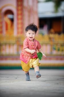 Bebé lindo feliz que corre al aire libre. tailandia