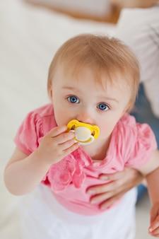Bebé lindo que mira la cámara mientras que está sostenido por su madre en una cama