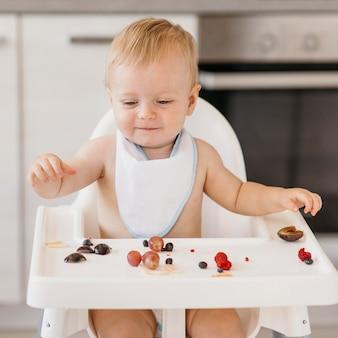 Bebé lindo sonriente comiendo solo