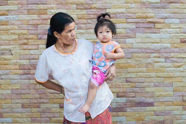 Bebé y madre asiáticos en textura del fondo del ladrillo