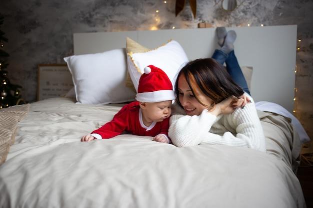 Bebé y madre en casa decorada de navidad