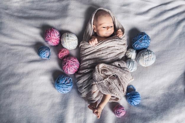 Bebé en manta yace en la cama entre enredos de hilo