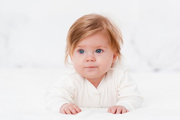 Bebé mirando a otro lado mientras posa