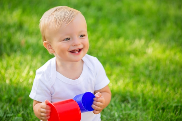 Bebé en un mono blanco sentado en la hierba verde jugando