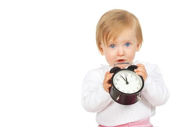 Bebé niña caucásica con reloj despertador negro aislado sobre fondo blanco.