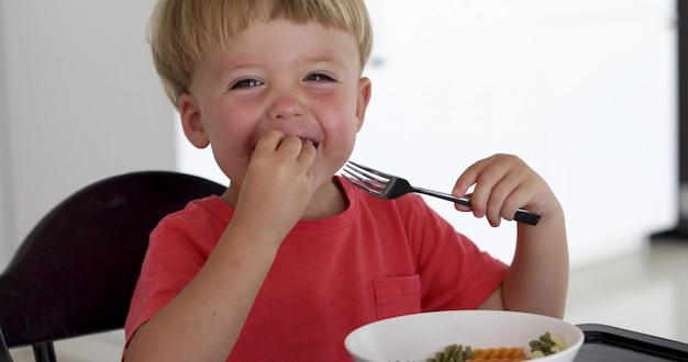 Bebé niño comiendo espaguetis en casa en la sala de estar