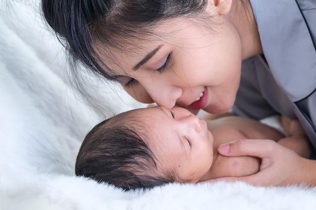 Un bebé de niño pequeño en un tierno abrazo de madre en la ventana