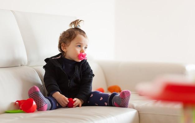 Bebé del niño del retrato que juega en el sofá.