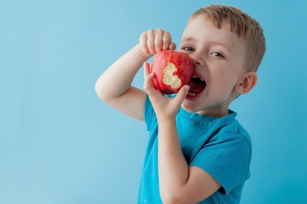 Bebé niño sosteniendo y comiendo manzana roja sobre azul