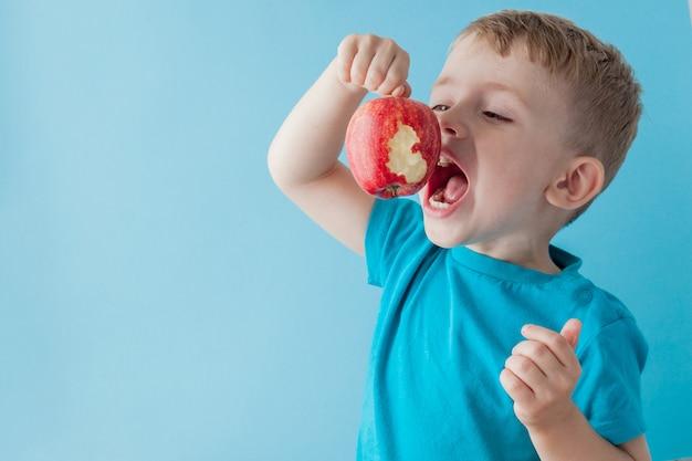 Bebé niño sosteniendo y comiendo manzana roja sobre fondo azul, comida, dieta y concepto de alimentación saludable