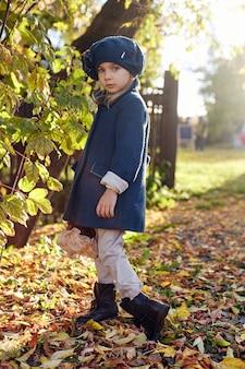 Bebé para niños en ropa retro primavera otoño. pequeño niño sentado sonriendo en la naturaleza