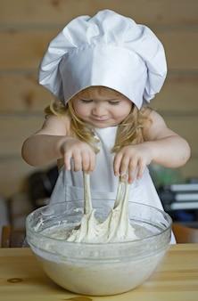 Bebé o niño en uniforme de cocinero con gorro de cocinero y delantal amasando masa con harina en un tazón de vidrio en la cocina