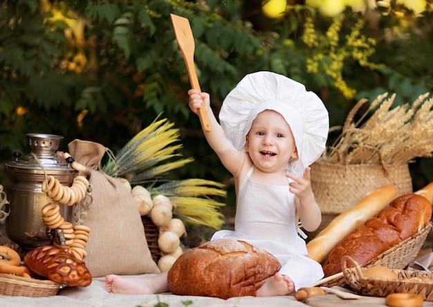 Bebé panadero cocina en la naturaleza. niño en un picnic come pan y rosquillas en un delantal blanco y sombrero