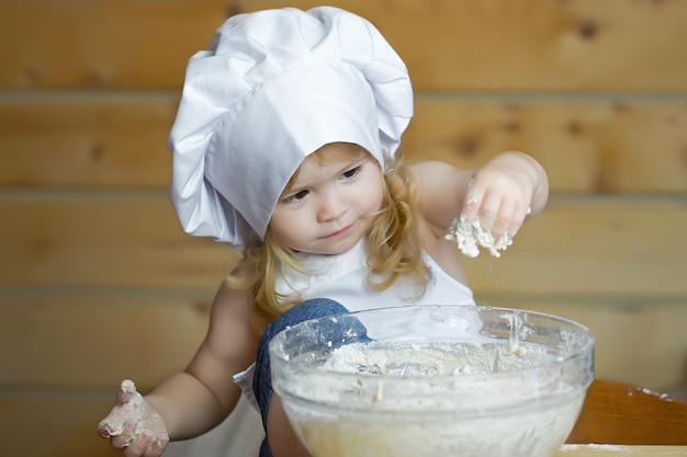 Bebé panadero o niño con cara feliz en uniforme de cocinero blanco con gorro de cocinero y delantal amasando masa con harina en un tazón de vidrio en la cocina de madera