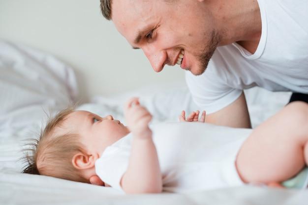 Bebé y papá mirándose en la cama