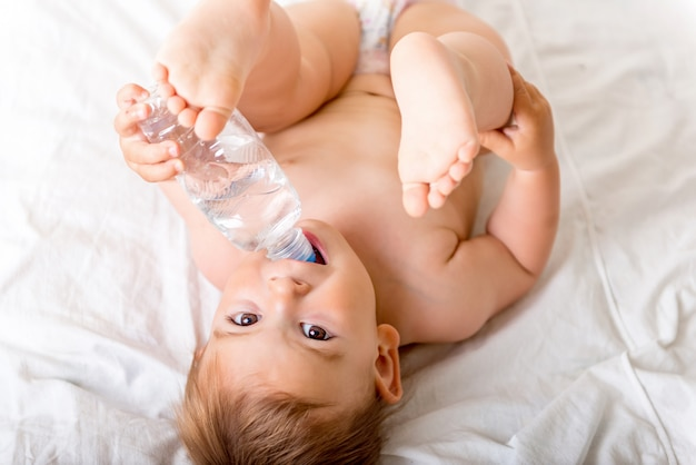 Bebé pequeño acostado en la cama blanca, sonríe y bebe agua de una botella de plástico.