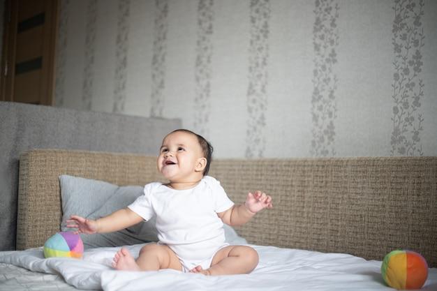 Bebé pequeño alegre jugando en una cama contra una pared bajo las luces de una habitación