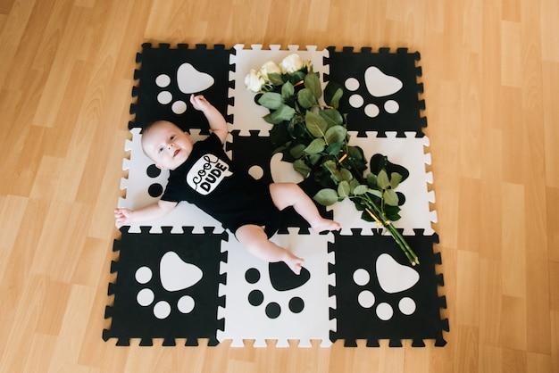 Bebé, un pequeño caballero miente en el desarrollo de la alfombra con un ramo de rosas, un regalo para el hombre en vacaciones