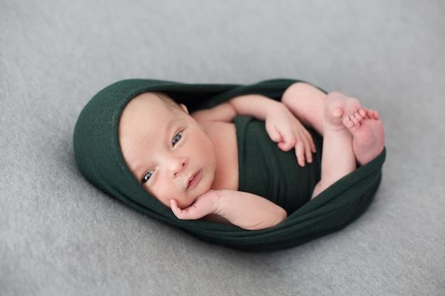 Un bebé pequeño envuelto con tejido negro streth.