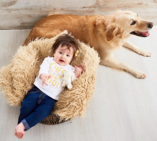 El bebé pequeño miente en la cesta cerca del perro
