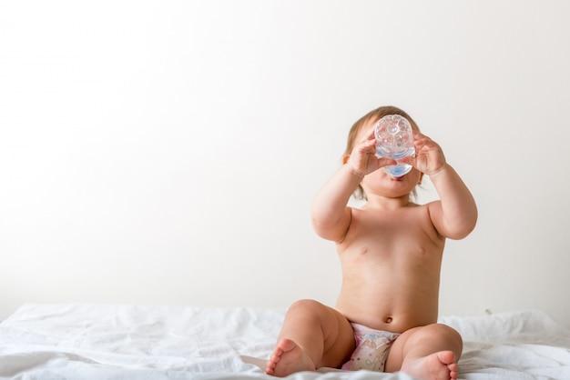 El bebé pequeño se sienta en la cama blanca, sonríe y bebe agua de una botella de plástico.