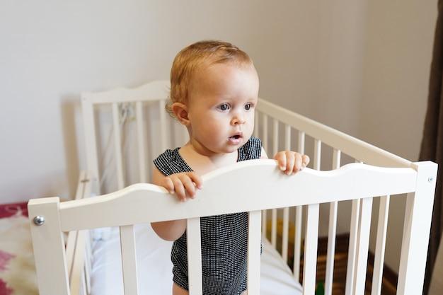 Bebé de pie en la cuna. linda niña, infancia