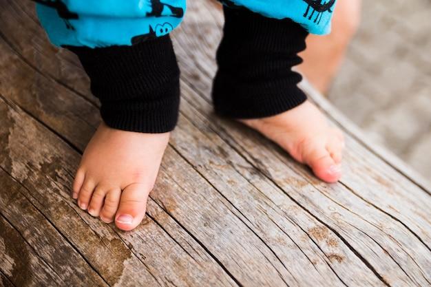 Bebé con los pies descalzos sobre el tronco del árbol.