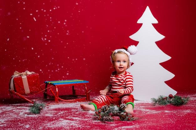 Bebé en pijama de navidad y sombrero de santa atrapa nieve sentado en un trineo con caja de regalo y gran árbol de navidad blanco sobre fondo rojo.