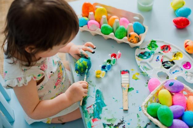 Bebé pintando huevos de pascua