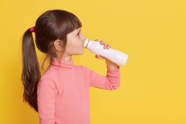Bebe poco leche mientras posa aislado en amarillo
