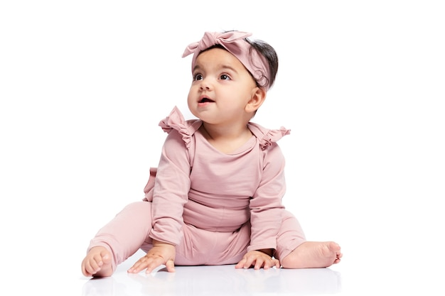 Bebé posando aislado en el piso blanco
