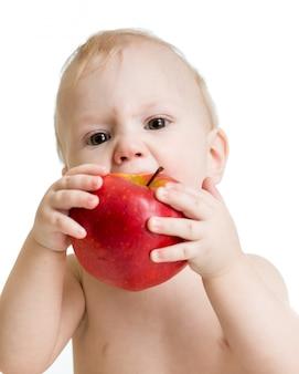 Bebé que come la manzana, aislada en blanco