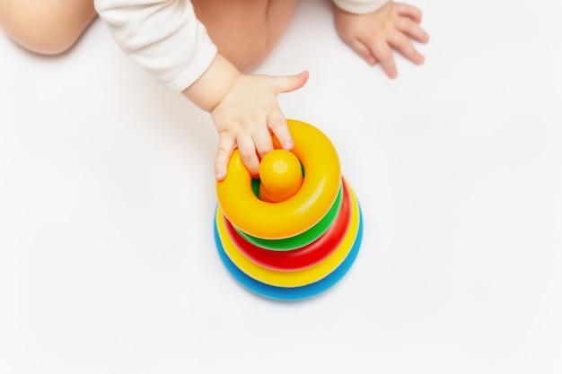 Bebé que juega con la pirámide colorida del juguete del arco iris. juguetes para niños pequeños. niño con juguete educativo. desarrollo infantil temprano