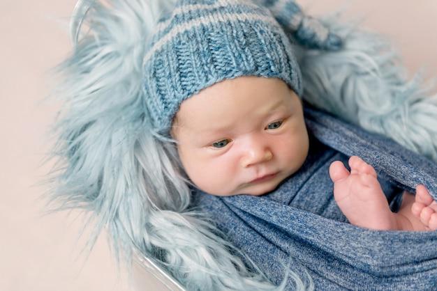 Bebé recién nacido acostado en el comedero con una manta azul