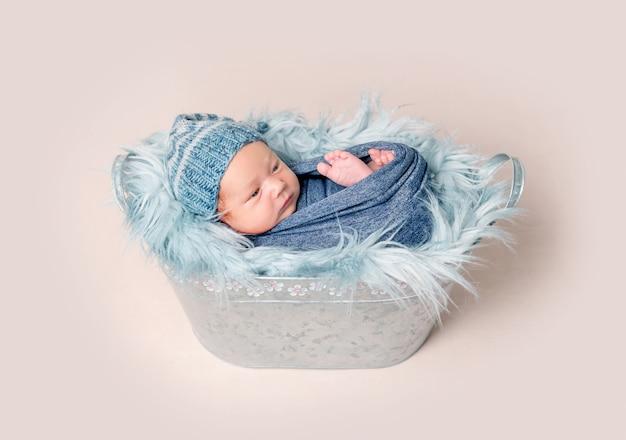 Bebé recién nacido acostado en un comedero con una manta