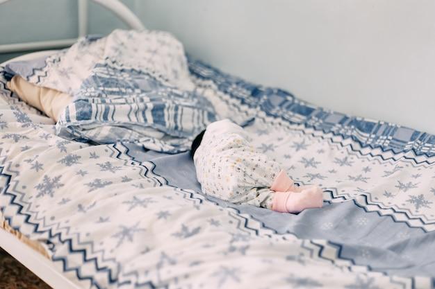 Bebé recién nacido acostado solo en la cama en el hospital