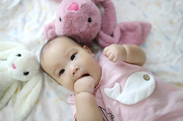 Bebé recién nacido asiático elegante lindo que duerme con el juguete del conejo del peluche en cama suave rosada en casa.