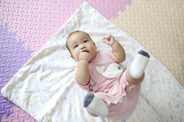 Bebé recién nacido asiático inteligente lindo que duerme con el juguete del conejo de peluche en cama suave rosada en casa.
