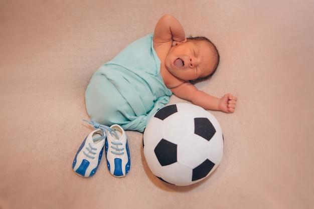 Bebé recién nacido y botitas de bebé con patrón de balón de fútbol.