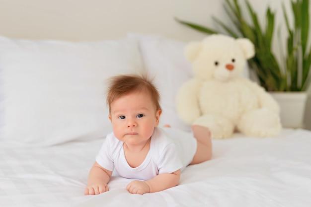 Bebé recién nacido descansando en la cama. el bebé se acuesta boca abajo en la cama con un oso de peluche