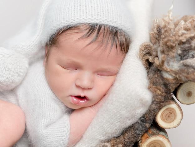 Bebé recién nacido dormido sobre el vientre acurrucado en la cuna