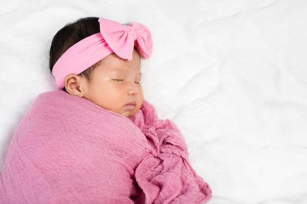 Bebé recién nacido duerme en una manta de abrigo de tela rosa en una cama